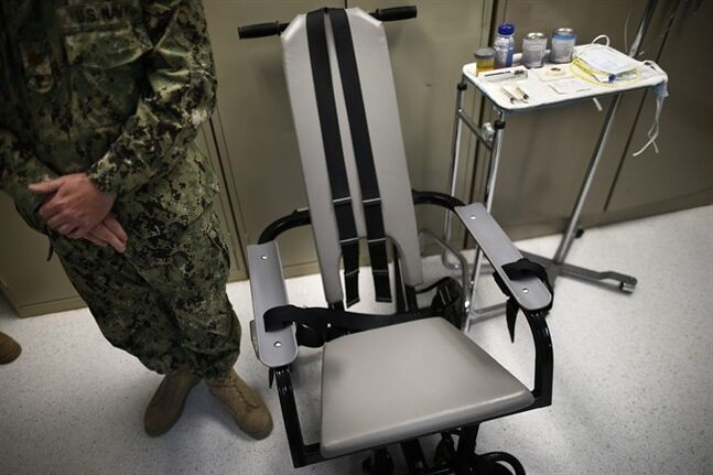 FILE - In this photo Nov. 20, 2013 file photo reviewed by the U.S. military, a U.S. Navy nurse stands next to a chair with restraints, used for force-feeding, and a tray displaying nutritional shakes, a tube for feeding through the nose, and lubricants, including a jar of olive oil, during a tour of the detainee hospital at Guantanamo Bay Naval Base in Cuba. Attorneys for a Syrian prisoner have begun studying hours of video showing him being removed from his cell, placed in a restraint chair and fed by a tube with liquid nutrients. They are looking for evidence of what he has portrayed to them as abusive force-feeding, akin to torture, during the months that he has participated in a hunger strike that drew the attention of President Barack Obama and led to a renewed effort to close the prison. (AP Photo/Charles Dharapak, File)