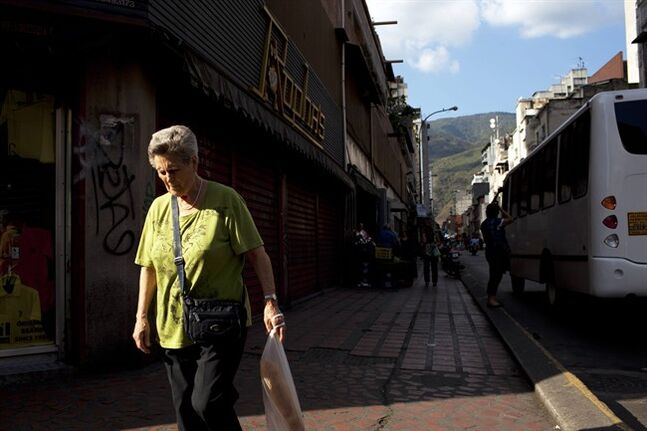 FILE - In this Feb. 20, 2014 file photo, a woman walks downtown after buying bread in Caracas, Venezuela. Venezuelans may soon have to scan their fingers to buy bread at the supermarket. President Nicolas Maduro announced late Wednesday, Aug. 20, 2014 a new, mandatory grocery fingerprinting system to combat food shortages. In the spring, Venezuela tried a similar system in government-run supermarkets on a voluntary basis. (AP Photo/Rodrigo Abd, File)