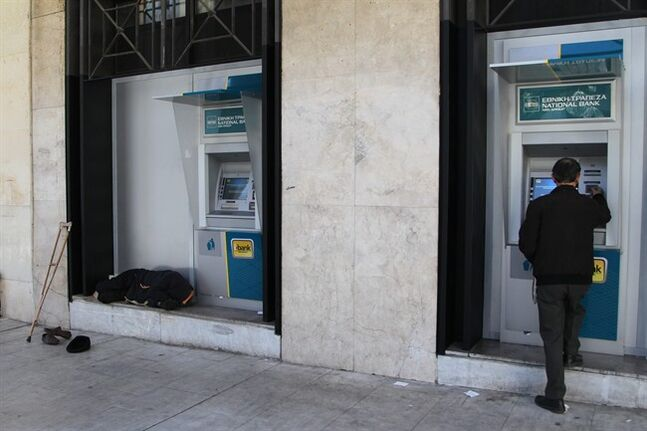 A person with disabilities sleeps next to ATM of National bank branch as a customer transacts in the northern Greek port of Thessaloniki, Wednesday, Jan. 29, 2014. (AP Photo/Nikolas Giakoumidis)