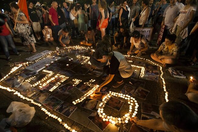 Israeli left wing activists light candles with shape of the word