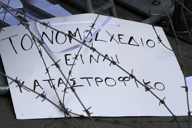 "A banner that reads in Greek ""The bill is disastrous"" is seen through barbed wire during a strike to protest government plans to privatize the state-run organizations in Nicosia, Cyprus, Thursday, Feb. 27, 2014. Hundreds of protesters have gathered outside Cyprus' parliament to voice opposition against legislation that will pave the way for the privatization of state-owned companies. (AP Photo/Petros Karadjias)"