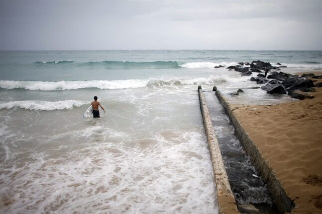 A surfer enters the water to take advantage of the high waves in San Juan, Puerto Rico, Saturday, Aug. 2, 2014. Bertha pushed just south of Puerto Rico on Saturday as it unleashed heavy rains and strong winds across the region.(AP Photo/Ricardo Arduengo)