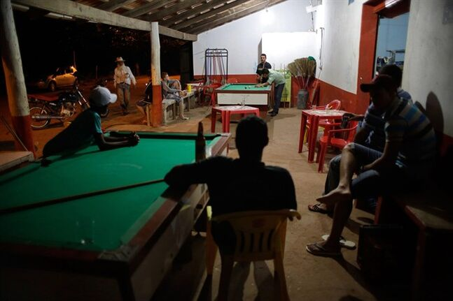 In this March 3, 2014 photo, residents gather for a night of play pool in the Araras community of Brazil's Goias state. Tucked into the sunbaked rolling hills of Brazil's midwest, Araras is home to what is thought to be the largest single group of people suffering from a rare inherited skin disease known as xeroderma pigmentosum, or