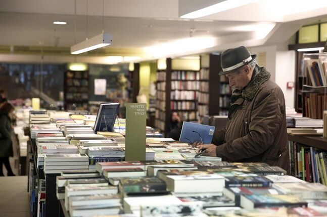 A customer of a bookstore checks some books in Athens Tuesday, Feb. 4, 2014. Leading Greek writers and publishers gathered at a bookstore in central Athens Tuesday to express their opposition to the proposed lifting of price controls on books sold in the recession-hit country. (AP Photo/Petros Giannakouris)