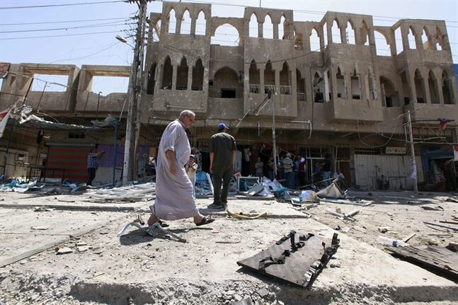 Civilians inspect the site of a bomb attack in the Jihad neighborhood in Baghdad, Saturday, July 19, 2014. A series of bombings, including three over a span of less than 10 minutes, killed and wounded dozens of people across Baghdad on Saturday, shaking the fragile sense of security the capital has maintained despite the Sunni militant offensive raging across northern and western Iraq. (AP Photo/Hadi Mizban)