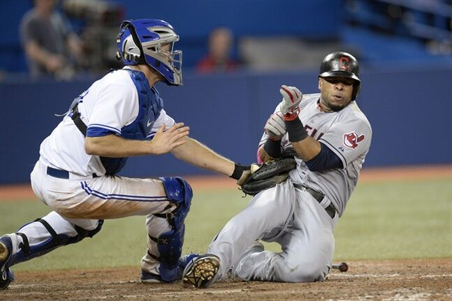 Toronto Blue Jays' Josh Thole tags out Cleveland Indians' Carlos Santana at home plate to end the top of the eighth inning American League baseball action in Toronto on Tuesday, May 13, 2014. THE CANADIAN PRESS/Frank Gunn