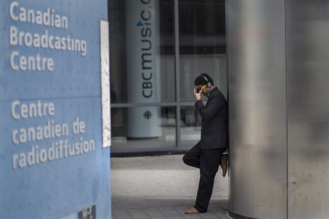 An unidentified man is pictured outside the CBC building in downtown Toronto is seen on Thursday June 26 2014. The broadcaster is expected to unveil a long-term plan to scale back its conventional television programming as part of a five-year shift toward more web and mobile broadcasting. THE CANADIAN PRESS/Chris Young