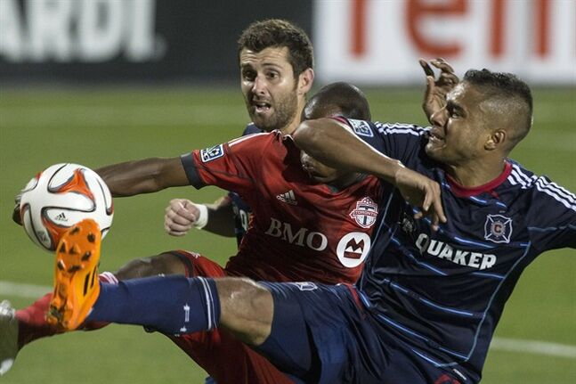 Chicago Fire's Quincy Amarikwa (right) and Gonzalo Segares (left) battle for the ball with Toronto FC 's Jackson Goncalves during second half MLS action in Toronto on Saturday August 23, 2014. THE CANADIAN PRESS/Chris Young