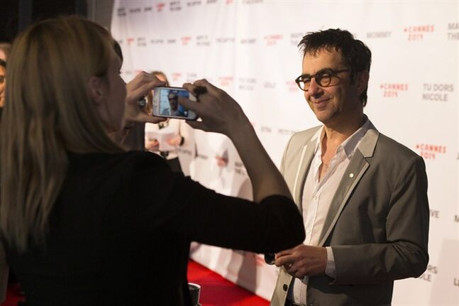 Film Director Atom Egoyan stops for a photograph on the red carpet as he arrives at a Canadian Film event in Toronto on Wednesday May 7, 2014 to discuss his movie 'The Captive' which has landed a competition slot for the Palme D'Or at this years' Cannes Film Festival. THE CANADIAN PRESS/Chris Young