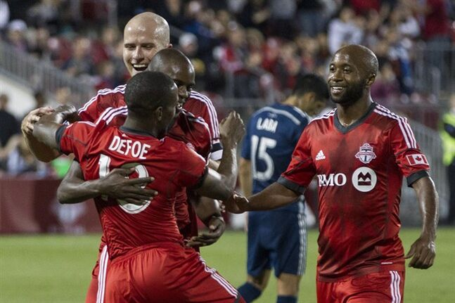Toronto FC's Jermain Defoe (centre left) celebrates with (left to right) Michael Bradley, Jackson Goncalves and Collen Warner after he scores from the penalty spot to level against Vancouver Whitecaps during second half MLS action in Toronto on Wednesday July 16, 2014. THE CANADIAN PRESS/Chris Young