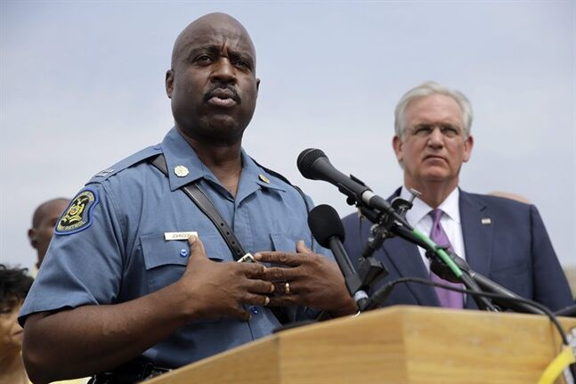 Capt. Ron Johnson of the Missouri Highway Patrol, left, answers questions as Gov. Jay Nixon listens during a news conference Friday, Aug. 15, 2014, in Ferguson, Mo. Nixon assigned protest oversight to Johnson, after violent protests in Ferguson erupted in the wake of the fatal shooting of Michael Brown by a police officer on Aug. 9. (AP Photo/Jeff Roberson)