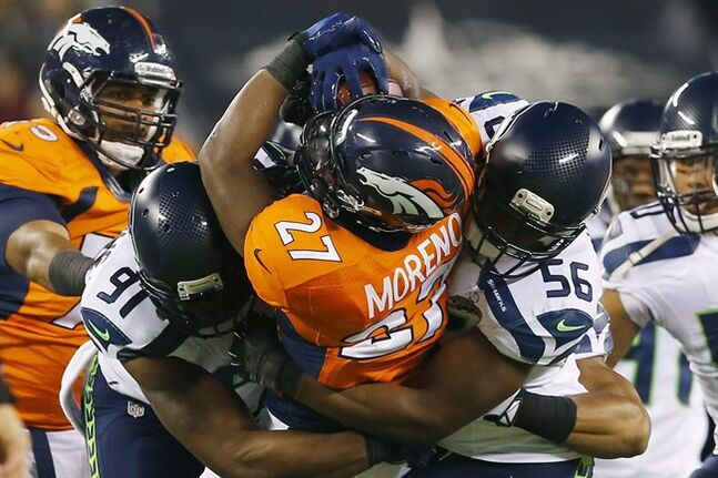 Denver Broncos' Knowshon Moreno is tackled by Seattle Seahawks' Chris Clemons, left, and Cliff Avril during the first half of the Super Bowl Sunday, Feb. 2, 2014, in East Rutherford, N.J. THE CANADIAN PRESS/AP, Paul Sancya