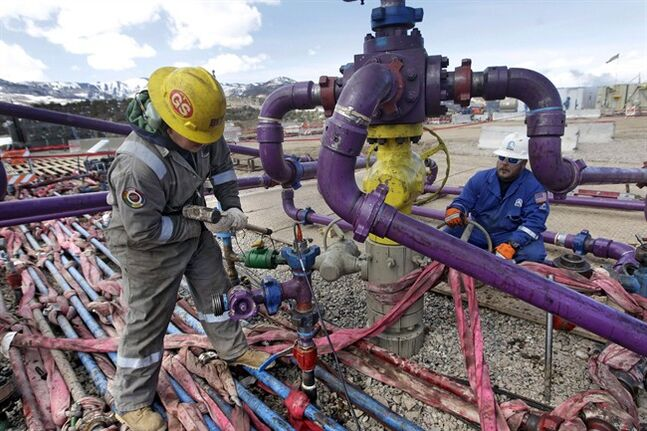 In this March 29, 2013 photo, workers tend to a well head during a hydraulic fracturing operation at an Encana Oil & Gas (USA) Inc. gas well outside Rifle, in western Colorado. THE CANADIAN PRESS/AP, Brennan Linsley