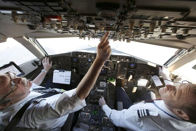 In this Dec. 10, 2013 photo, American Airlines Capt. Paul Wannberg, left, and First Officer Robert Popp prepare a Boeing 757 jet for takeoff in Grapevine, Texas. THE CANADIAN PRESS/AP, LM Otero
