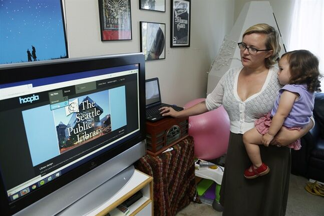 In this Sept. 11, 2013 photo, Jamie Koepnick-Herrera holds her daughter Paloma as they browse for a video to watch. THE CANADIAN PRESS/AP, Ted S. Warren