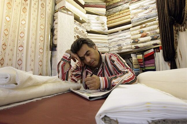 In this picture taken on July 14, 2012, an Iranian textile merchant works on a crossword puzzle, as he waits for customer in Tehran's old main bazaar. THE CANADIAN PRESS/AP, Vahid Salemi