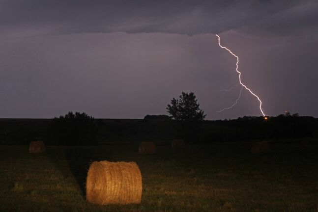 Lightning strikes in the distance behind a field of hay bales near Highway 1 west of Brandon during a thunderstorm a few years ago.