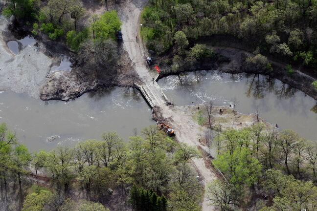 In this file photo, clean-up crews work to restore Victoria Park in Souris, including a bridge over Plum Creek.The park was heavily damaged in 2011's flood.