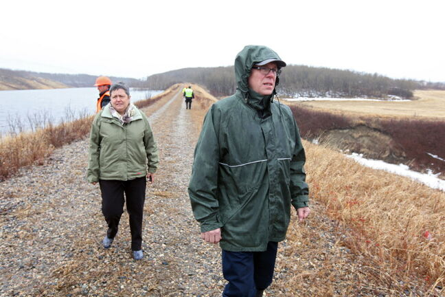 Riding Mountain MLA Leanne Rowat and Manitoba Premier Greg Selinger walk along the embankment on a tributary to Birdtail Creek in Waywayseecappo First Nation to get a sense of how much water is building up against it and where it is failing on Monday afternoon.