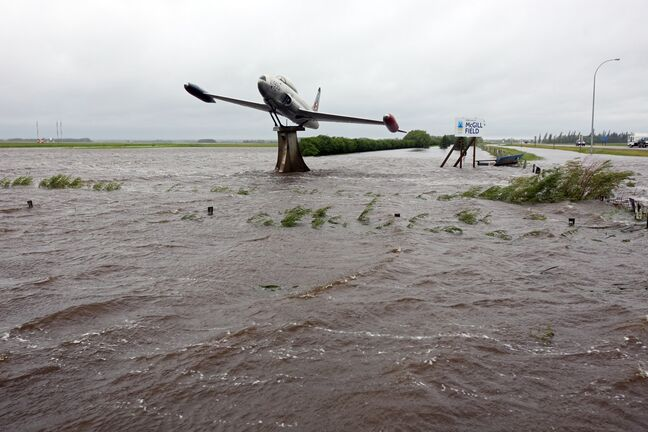 Overland flooding surrounds a T33 fighter jet on display along Highway 10 and Sandison Road near the Brandon Municipal Airport on Sunday after rain fell almost non-stop throughout the weekend. The airport was closed due to the flooding.