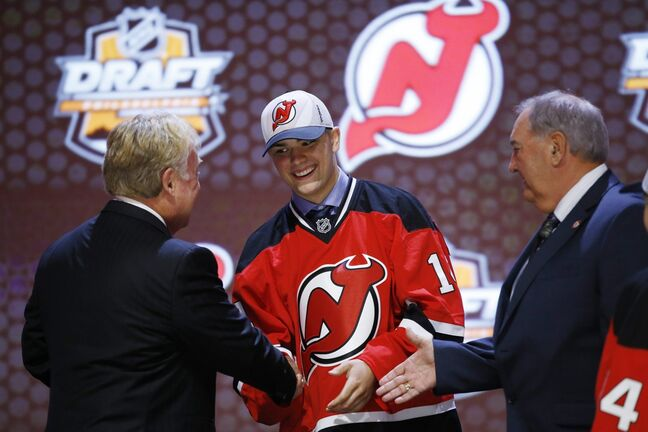 Wheat Kings centre John Quenneville shakes hands with New Jersey Devils officials after being chosen 30th overall during the first round of the NHL hockey draft.
