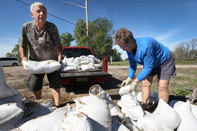 Terry Hutchinson, left, and Betty Grangersling help with sandbagging efforts at East Delta Beach Monday.