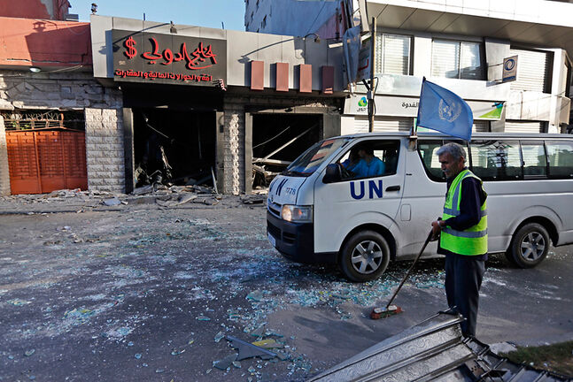 A Palestinian worker sweeps the streets from glass, as a United Nations vehicle drives past a damaged money exchange post, following an overnight Israeli missile strike in Gaza City on Thursday.