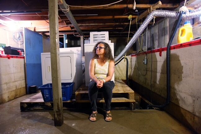 Jean Halliday sits in her basement, still wet from recent overland flooding, in her home on 16th Street North in Brandon on Tuesday.