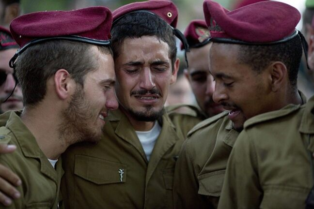 Israeli soldiers of the Paratroopers Brigade mourn over the grave of Sgt. Bnaya Rubel during his funeral at the military cemetery in Holon, Israel, Sunday. Rubel was killed while fighting Palestinian militants in Gaza on Saturday.