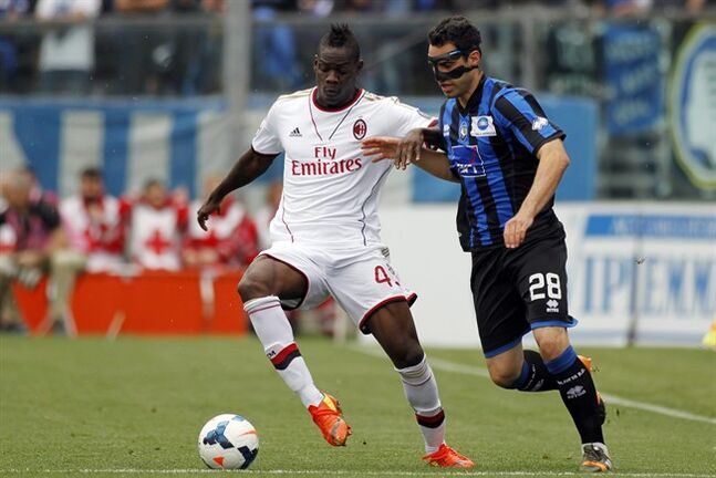 AC Milan's Mario Balotelli, left, is challenged by Atalanta's Davide Brivio during a Serie A soccer match in Bergamo, Italy, Sunday, May 11, 2014. (AP Photo/Felice Calabro')