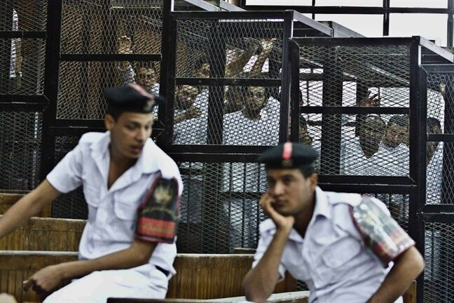 """File - In this file photo taken Thursday, May 15, 2014, Al-Jazeera's Egyptian journalist Abdullah Elshamy, center, appears in a defendants' cage along with several other defendants in a courthouse during a trial on terror charges in Cairo, Egypt. On Wednesday, July 23, an Egyptian judge released his reasoning for harsh sentences issued against three Al-Jazeera journalists, saying they were brought together """"by the devil"""" to fake news reports with the aim of destabilizing the country. (AP Photo/Hamada Elrasam, File)"""