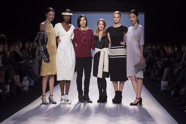 Designers Malorie Urbanovitch, centre right, and Cecile Raizonville of Matiere Noire, centre left, stand on the the runway after their shared first place in the