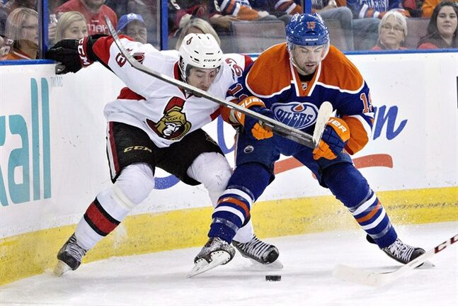 Ottawa Senators' Mika Zibanejad (93) battles for the puck with Edmonton Oilers' Justin Schultz (19) during first period NHL hockey action in Edmonton, Alta., on Tuesday, March 4, 2014. THE CANADIAN PRESS/Jason Franson