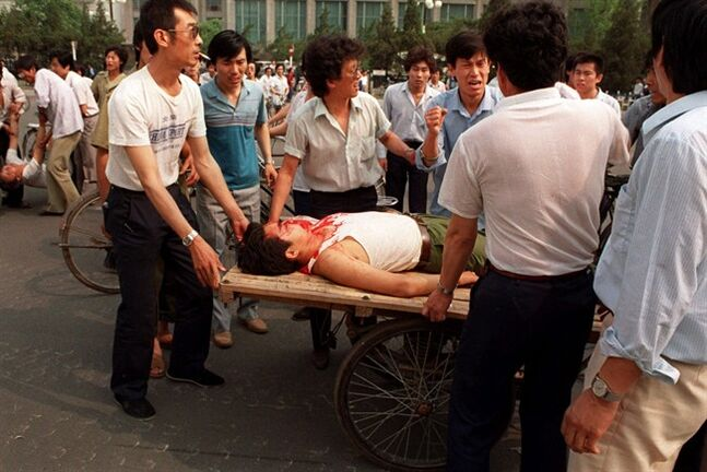 Beijing residents load a wounded person on a rickshaw flatbed shortly after Chinese soldiers opened fire on a crowd in Tienanmen Square in this June 4, 1989 photo. THE CANADIAN PRESS/AP- Liu Heung Shing