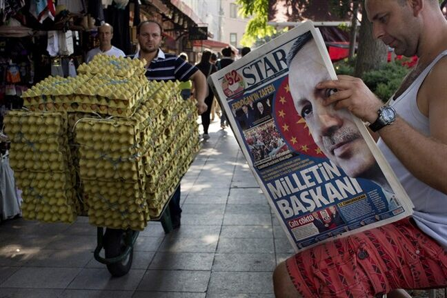 A man reads a newspaper in central Istanbul, Turkey, on Monday, Aug. 11, 2014. Erdogan won Turkey's first direct presidential election Sunday, striking a conciliatory tone toward critics who fear he is bent on a power grab as he embarks on another five years at the country's helm. The newspaper's front page headline reads a