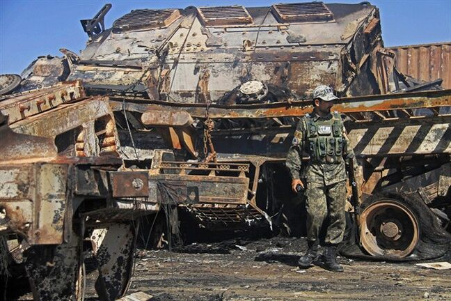 An Afghan policeman stands near a destroyed NATO supply truck in Behsud district of Jalalabad east of Kabul, Afghanistan, Monday, June 9, 2014. An Afghan provincial official says suicide bombers have attacked a parking lot at a police base in eastern Afghanistan, killing a guard and setting almost two dozen trucks ablaze. (AP Photo/Nisar Ahmad)