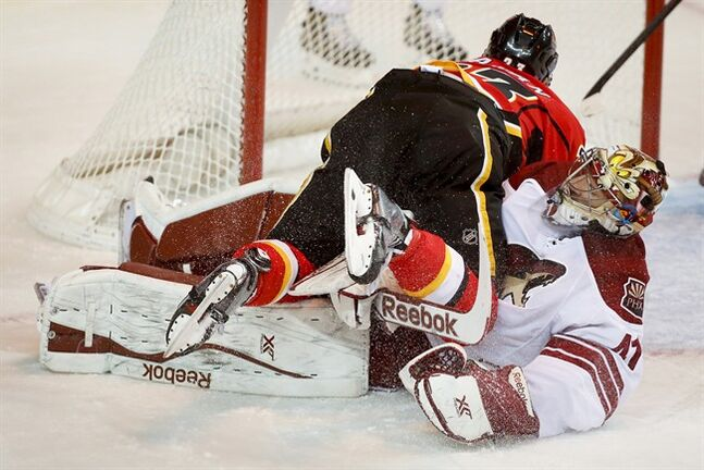 Phoenix Coyotes goalie Mike Smith, right, looks on as Calgary Flames' Sean Monahan crashes over him after scoring during first period NHL hockey action in Calgary, Alta., Wednesday, Jan. 22, 2014.THE CANADIAN PRESS/Jeff McIntosh
