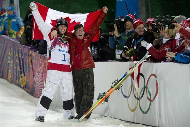 Canadian Alex Bilodeau, left, celebrates his win gold medal win with his brother Frederic following the moguls finals at the Sochi Winter Olympics in Krasnaya Polyana, Russia, Monday, Feb. 10, 2014. THE CANADIAN PRESS/Jonathan Hayward