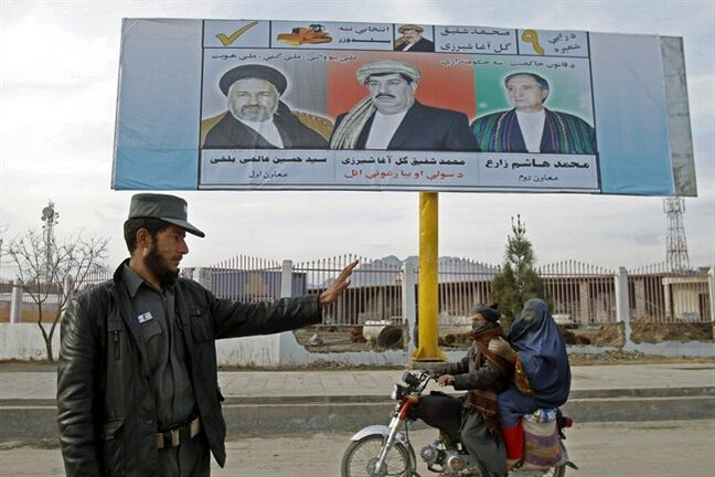 An Afghan policeman stands guard at a temporary checkpoint as a man on a motorcycle rides past an election poster of presidential candidate, Mohammad Shafiq Gul Agha Sherzai, center, in Kandahar, south of Kabul, Afghanistan, Sunday, Feb. 9, 2014. (AP Photo/Allauddin Khan)