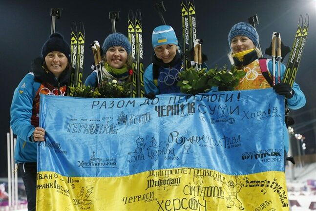 FILE - In this Friday, Feb. 21, 2014, file photo Ukraine's relay team Vita Semerenko, Juliya Dzhyma, Olena Pidhrushna and Valj Semerenko, from left, celebrate with a Ukrainian flag with writings on it after winning the gold during the women's biathlon 4x6k relay, at the 2014 Winter Olympics in Krasnaya Polyana, Russia. The Ukrainian city of Lviv withdrew its bid for the 2022 Winter Olympics on Monday June 30, 2014, becoming the third contender to drop out of the race for a games that no one seems to want. (AP Photo/Dmitry Lovetsky, File)
