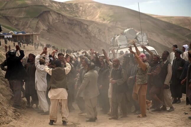 Survivors of Friday's landslide participate in a rally after police fired in the air to disperse a crowd that had rushed toward a truck carrying aid, near the site of Abi Barik village in Badakhshan province, northeastern Afghanistan, Tuesday, May 6, 2014. Many Abi Barik villagers have complained that aid has been slow to arrive while officials have said their efforts have been complicated by villagers from nearby areas coming to get handouts. (AP Photo/Massoud Hossaini)