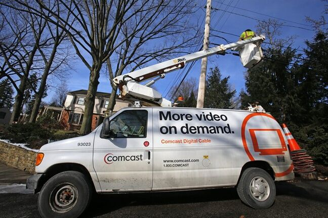 In this Thursday, Jan. 9, 2014, photo, a Comcast cable truck works in front of a home in Mount Lebanon, Pa. Comcast reports quarterly earnings on Tuesday, Jan. 28, 2014.(AP Photo/Gene J. Puskar)