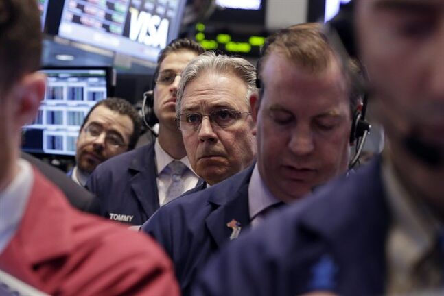 Thomas Kaye, third from right, works with fellow traders on the floor of the New York Stock Exchange Friday, May 16, 2014. Just a few months ago, investors thought the economy would expand rapidly this year. Now they're not so sure and shifting their money around in surprising ways in a sign that a fragile confidence still haunts the recovery five years after it officially began. (AP Photo/Richard Drew)