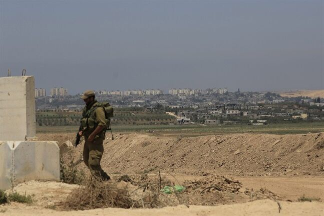 Part of the Gaza Strip looks over an Israeli reserve soldier walking outside a military post near the Israel Gaza border on Thursday, Aug. 7, 2014. (AP Photo/Tsafrir Abayov)