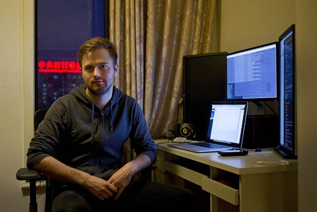 """In this Sunday, June 1, 2014 photo, Nils Pihl sits next to a work station at his apartment, which he converted to an office in Beijing, China. Pihl has spent 18 months building what he calls cutting-edge software to crunch """"really big data sets."""" But instead of going to Silicon Valley, the 27-year-old Swede and his four colleagues have been working on his invention from a small apartment overlooking smoggy northwest Beijing. (AP Photo/Andy Wong)"""