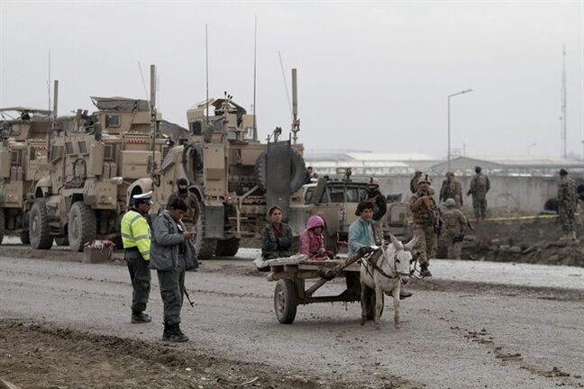 Afghan children travel on a donkey cart near a gate used by NATO troops in Kabul, Afghanistan, Wednesday, Dec. 11, 2013. The Afghan Interior Ministry says a car bomb has exploded near a gate used by NATO troops in the northern section of the Kabul airport. There were no casualties in the attack. (AP Photo/Rahmat Gul)