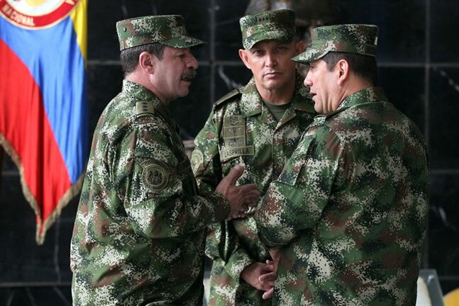 The new Colombian armed forces commander Gen. Juan Pablo Rodriguez, right, talks to newly appointed chief of staff Gen. Javier Florez, left, and army commander Gen. Jaime Lasprilla, center, after a press conference where Defense Minister Juan Carlos Pinzon announced the firing of the fromer armed forces chief Gen. Leonardo Barrero in Bogota, Colombia, Tuesday, Feb. 18, 2014. Gen. Barrero was fired for verbally maligning prosecutors investigating extrajudicial executions. (AP Photo/Fernando Vergara)