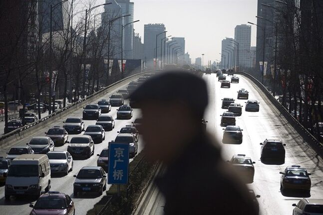 A man walks past a city ring road clogged with heavy traffic in Beijing Thursday, Jan. 9, 2014. THE CANADIAN PRESS/AP, Andy Wong