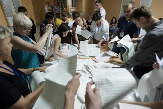 Election commission officials count ballots at a polling station in Kiev, Ukraine, on Sunday, May 25, 2014. Ukraine's critical presidential election went underway Sunday under the wary scrutiny of a world eager for stability in a country. An exit poll showed that billionaire candy-maker Petro Poroshenko won election in the first round. (AP Photo/Evgeniy Maloletka)