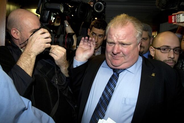 Toronto Mayor Rob Ford pushes through a media scrum at City Hall in Toronto on Wednesday January 22, 2014. Ford is being sued by his sister's ex-boyfriend for allegedly conspiring to have the man beaten in jail.THE CANADIAN PRESS/Frank Gunn